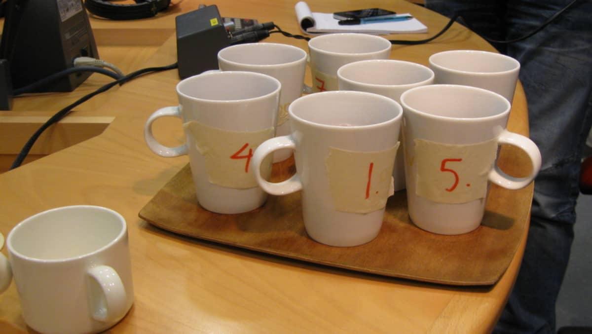 pöydällä numeroituja kahvimukeja tarjottimella