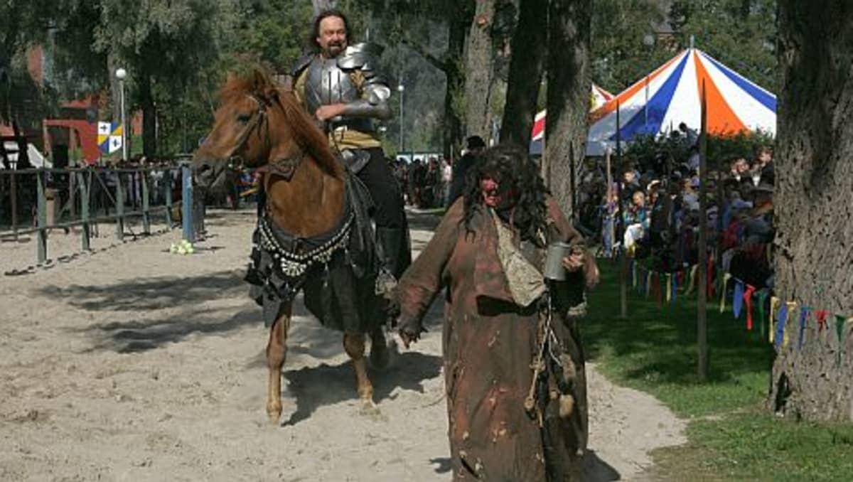 keskiaikamarkkinoilla mies ratsailla ritariasussa, nainen ryysyissä tuoppi kädessä