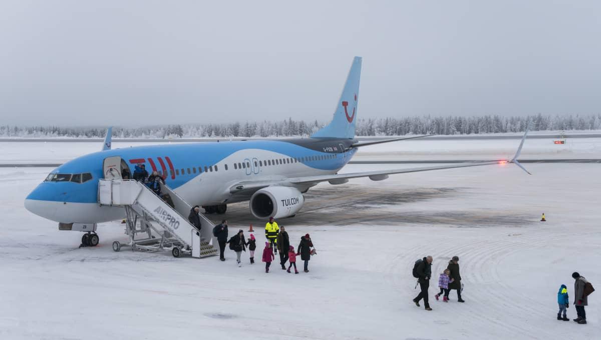 Jouluturisteja tulossa koneesta Rovaniemen lentokentällä