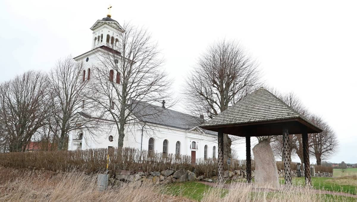 Valkoinen kirkko ja kiviaita, jonka edessä seisoo riimukivi katoksen alla.