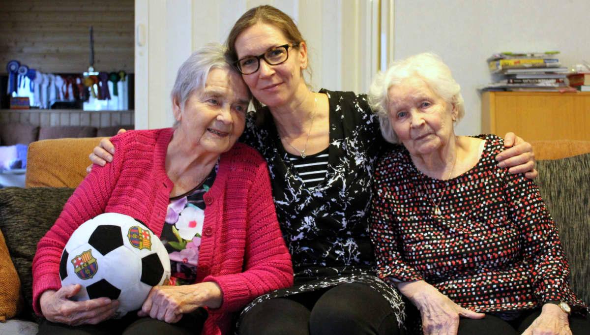 Kaksi ikäihmistä perhehoitajan kainalossa sohvalla.