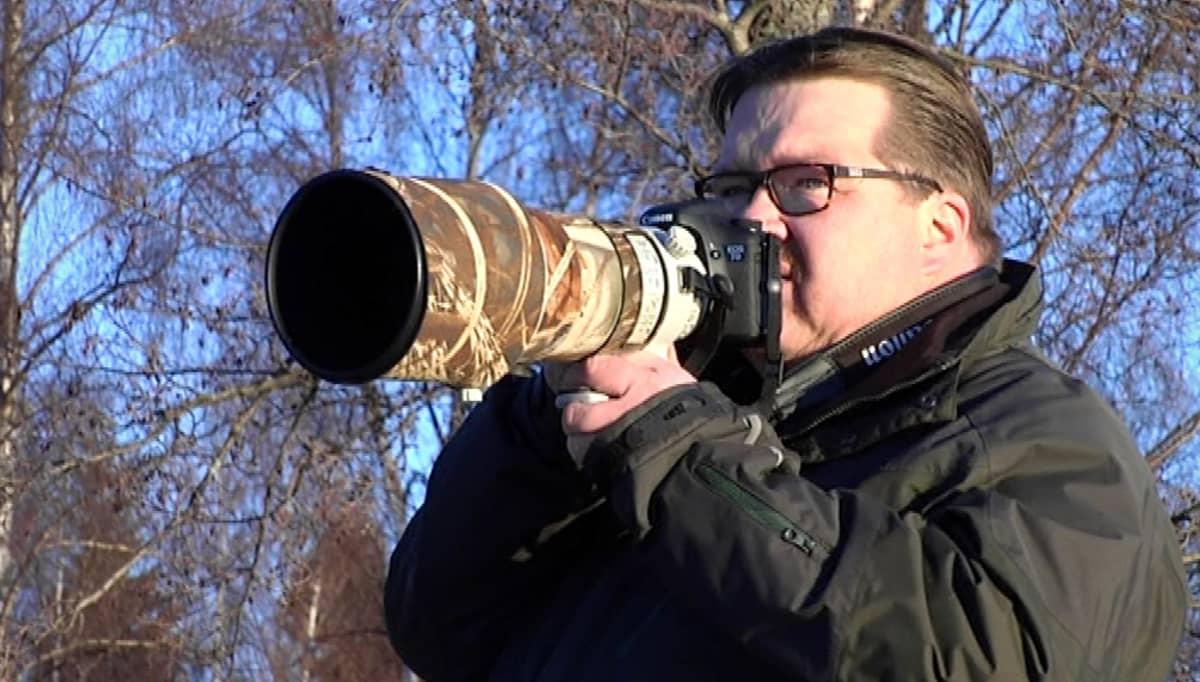 Mies on valmiina kuvaamaan järjestelmäkamerallaan.