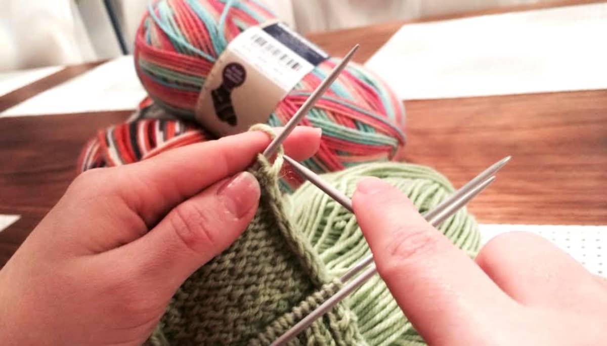 Nainen neuloo villasukkia.