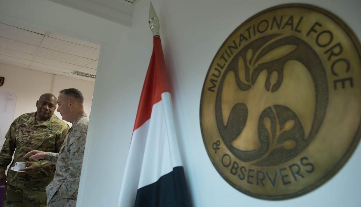 MFO:n logo, taustalla sotilaita.