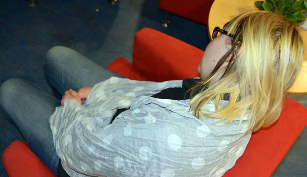 Kuvassa nojatuolissa torkkuva nainen.