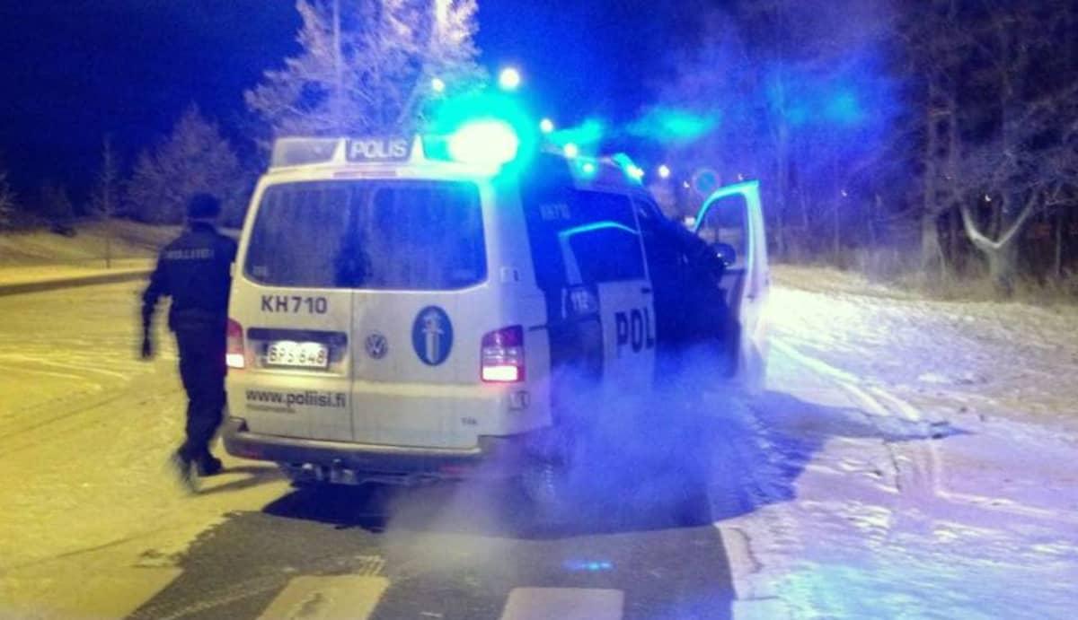 Poliisiautossa vilkut päällä ja kaksi miestä nousemassa autoon
