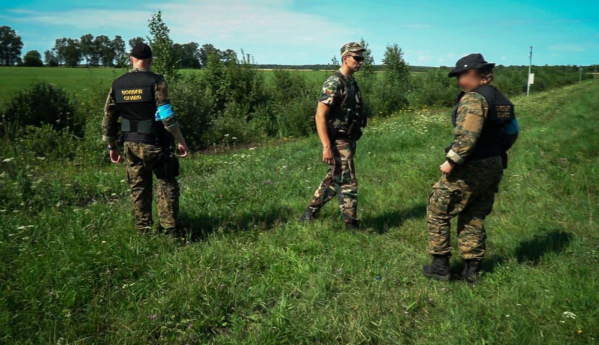 Liettualainen rajavartija opastaa suomalaisia. Tässä kohtaa Liettuan ja Valko-Venäjän erottaa vain kapea oja.
