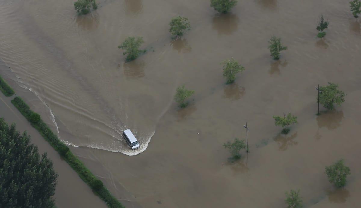 Auto ajoi pois Han-joen tulvan peittämältä parkkialueelta Soulissa torstaina.