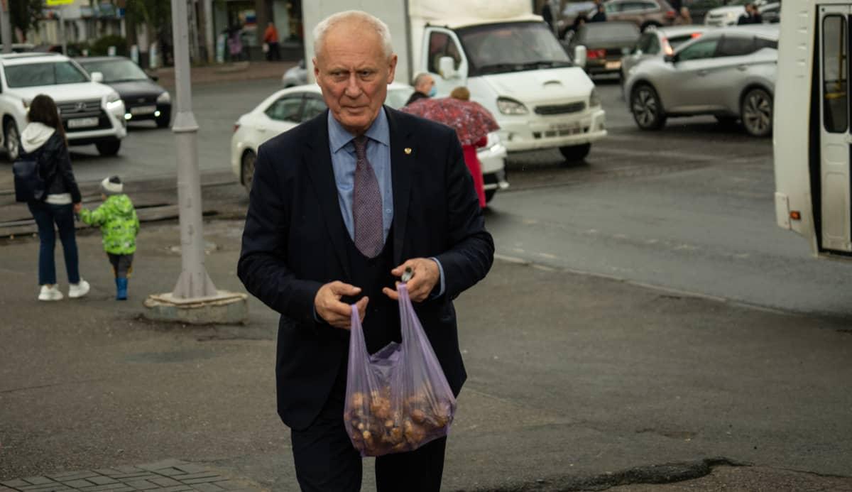 Vanha mies kädessään muovipussi