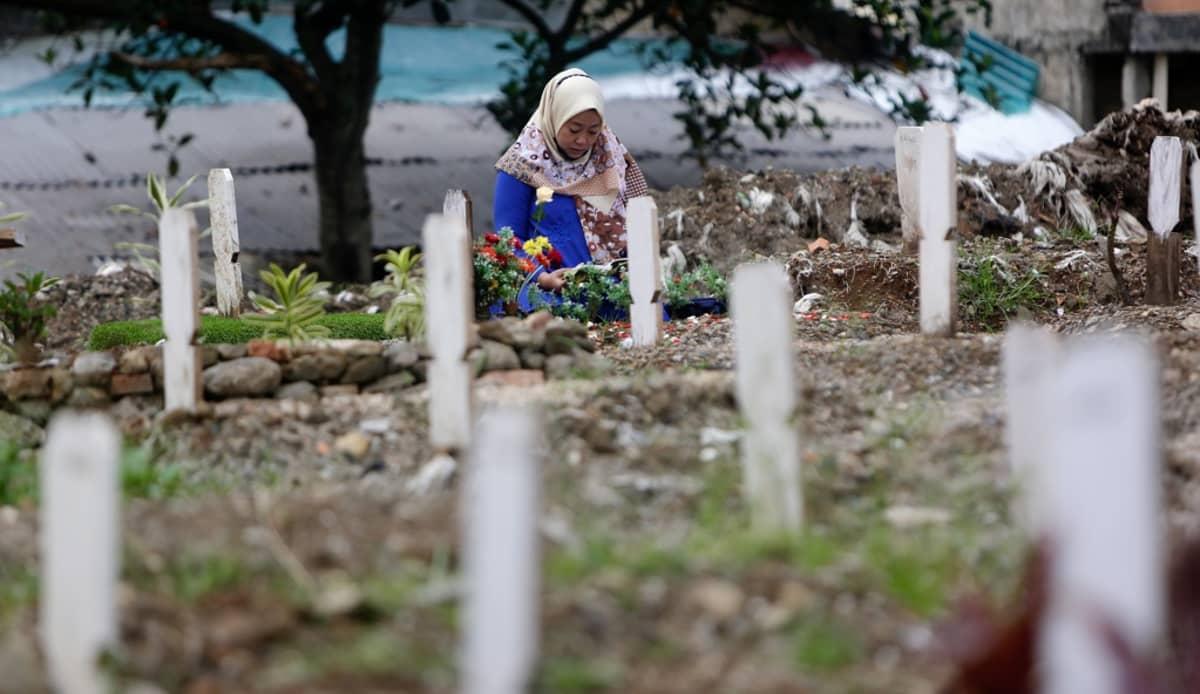 Nainen polvillaan haudalla, etualalla valkoisen hautamerkkien rivi.