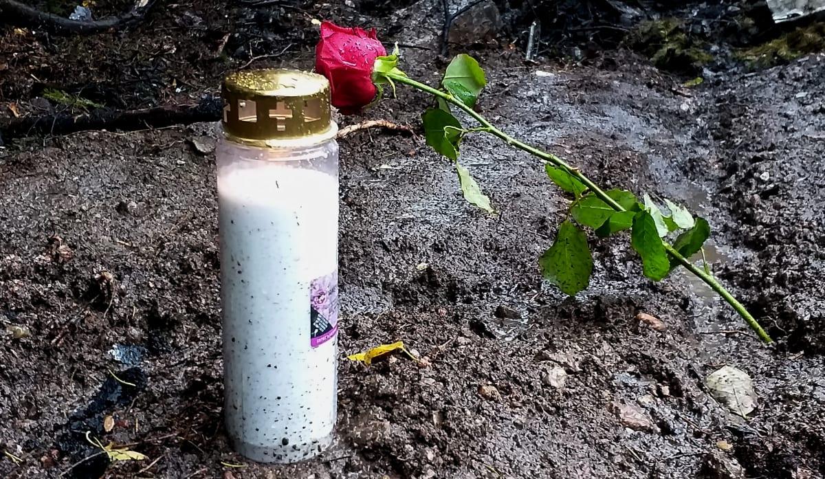 Muistokynttilä  ja punainen ruusu maassa.
