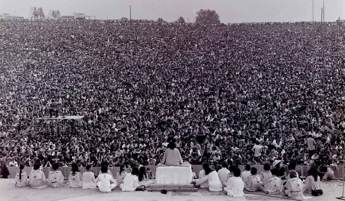 Mustavalkoinen kuva suuresta nuorisojoukosta, jonka edessä istuu valkopukuinen mies.