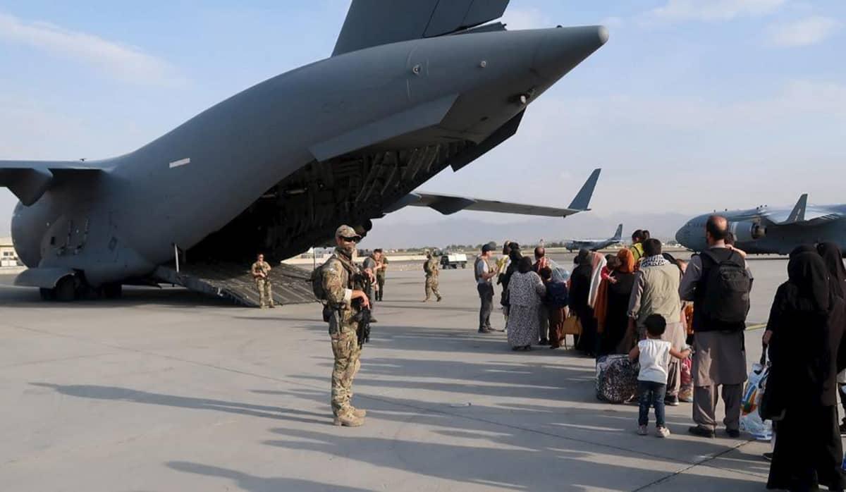Puolustusvoimien suojausjoukon sotilaita ja evakuoitavia ihmisiä Kabulin lentokentän alueella Afganistanissa.