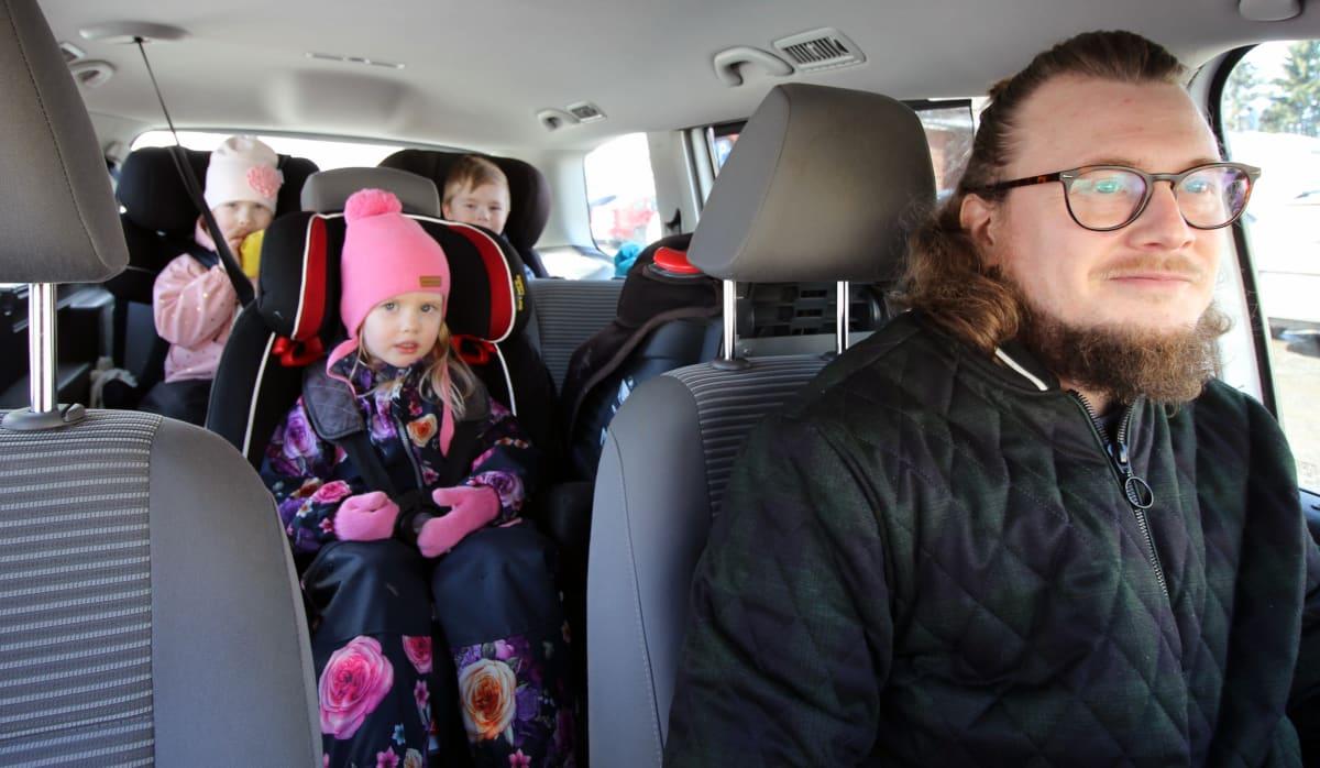 Jaakko Palmunen auton ratissa, lapset takapenkillä.