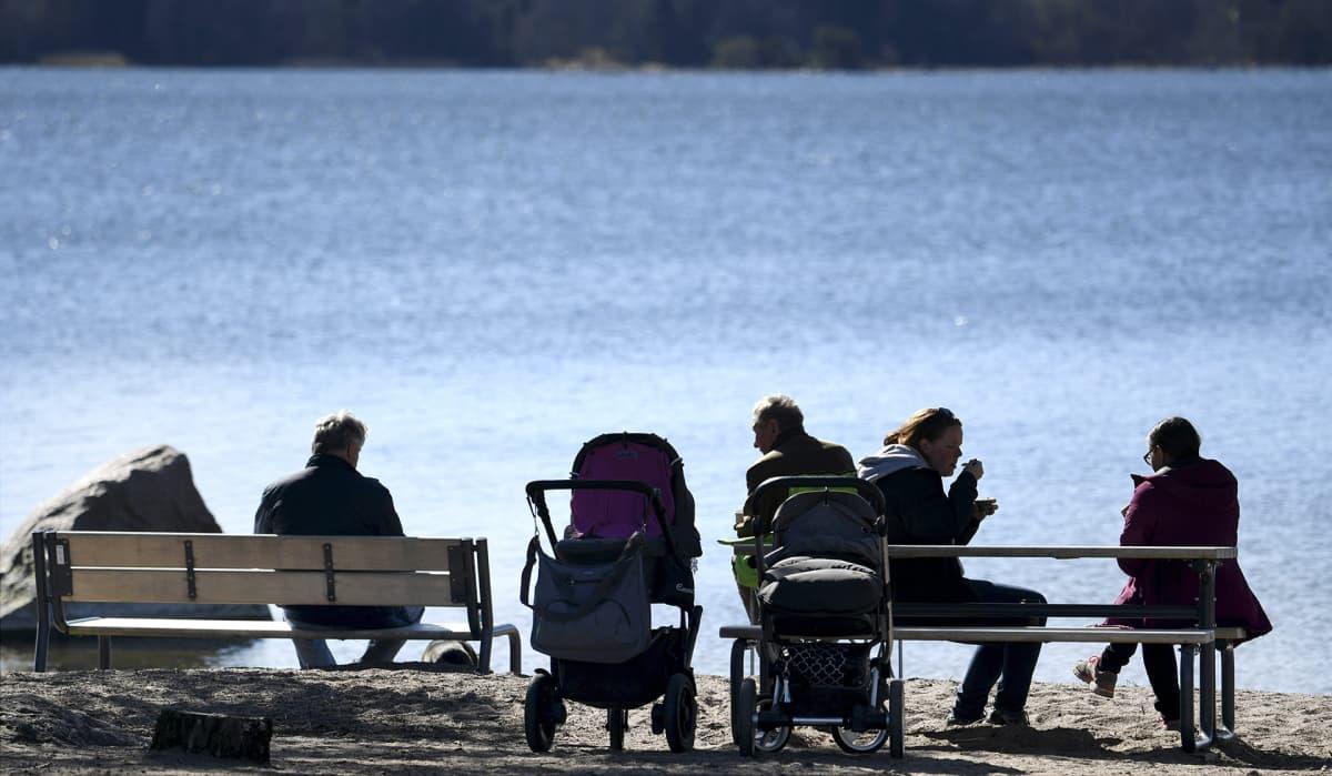 Ulkoilijoita nauttimassa aurinkoisesta säästä Mellesteninrannassa Espoossa 21. huhtikuuta