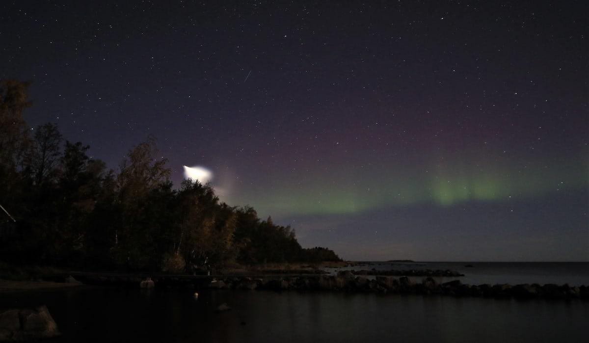 Öinen taivaanranta, jossa vasemmalla kirkas valopallo ja oikealla revontulia.