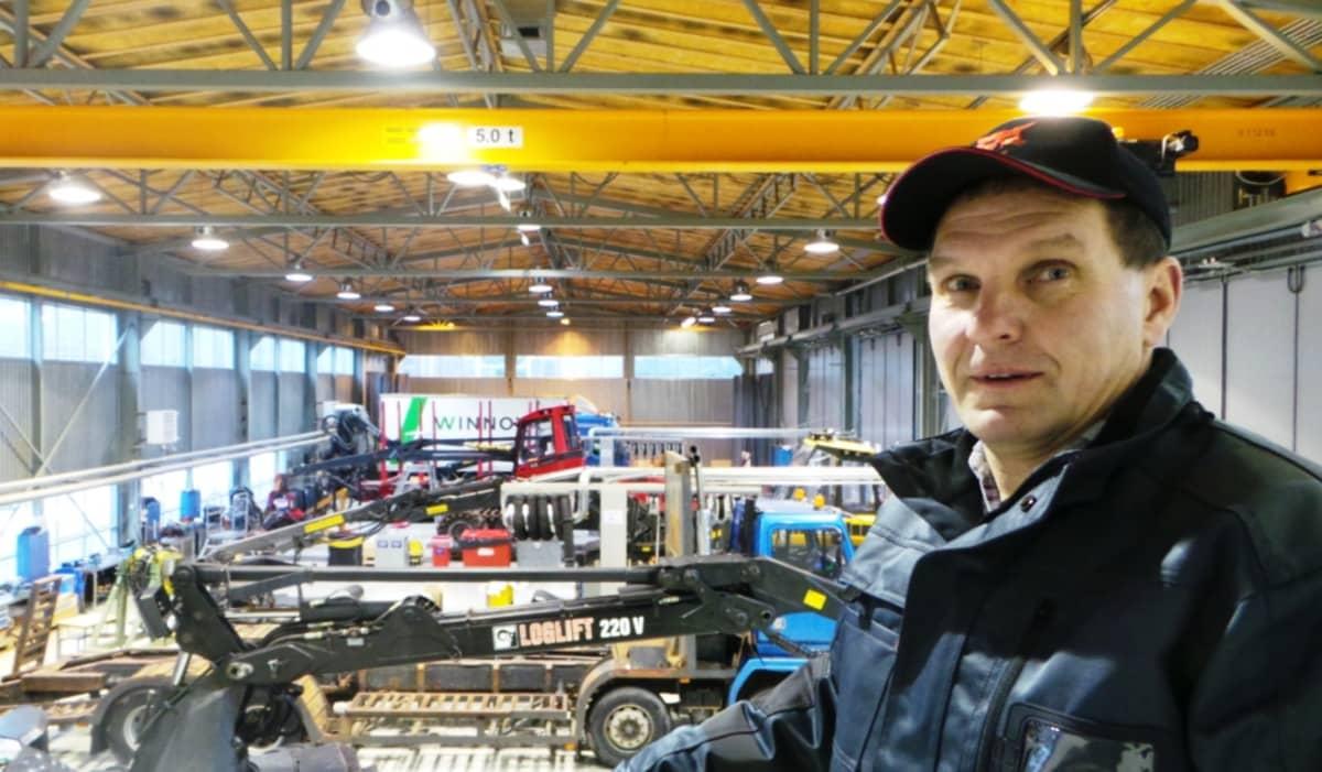 mies seisoo hallissa jossa on metsäkoneita ja kuorma-autoja