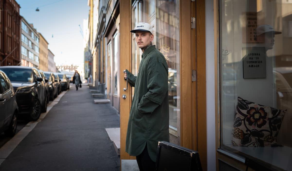 Johannes Poikkimäki seisoo aukinaisen oven vieressä.