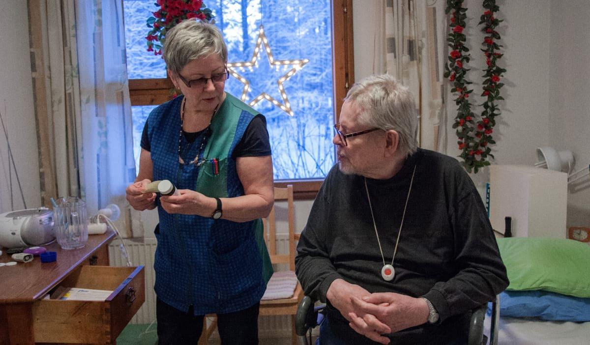 Kotihoitaja Paula Keränen laskee lääkkeitä 78-vuotiaalle Paavo Karjalaiselle Hyrynsalmella.