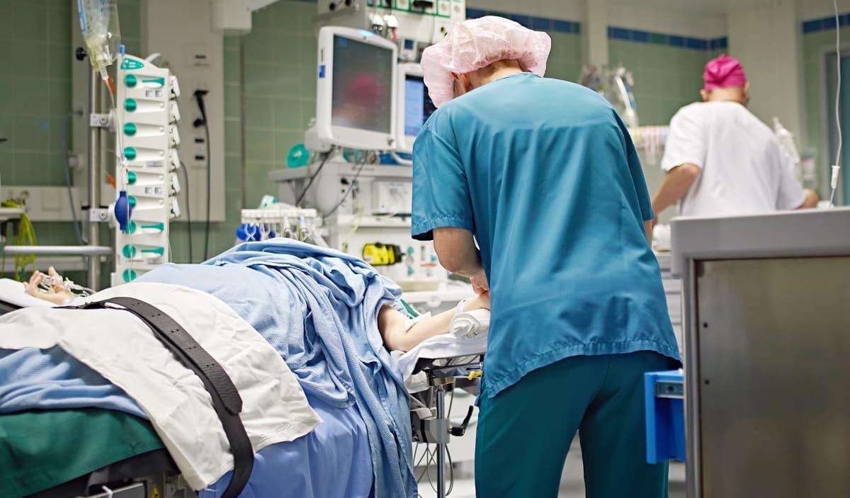 Hoitaja valmistelee potilasta leikkaukseen.