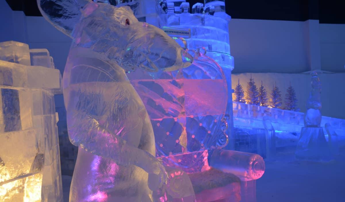 Rottaa esittävä jääveistos etualalla, taustalla jäästä tehty istuin ja jäälinna.