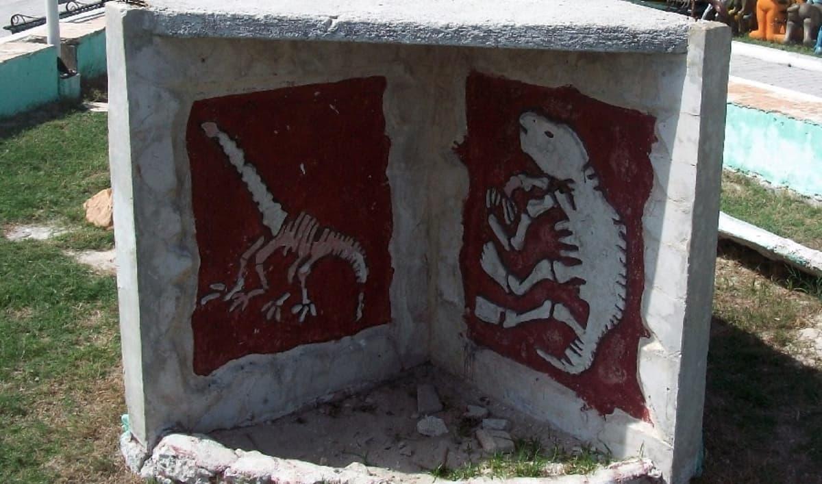 Betoninen muistomerkki, johon on maalattu kahden dinosauruksen luurangot.