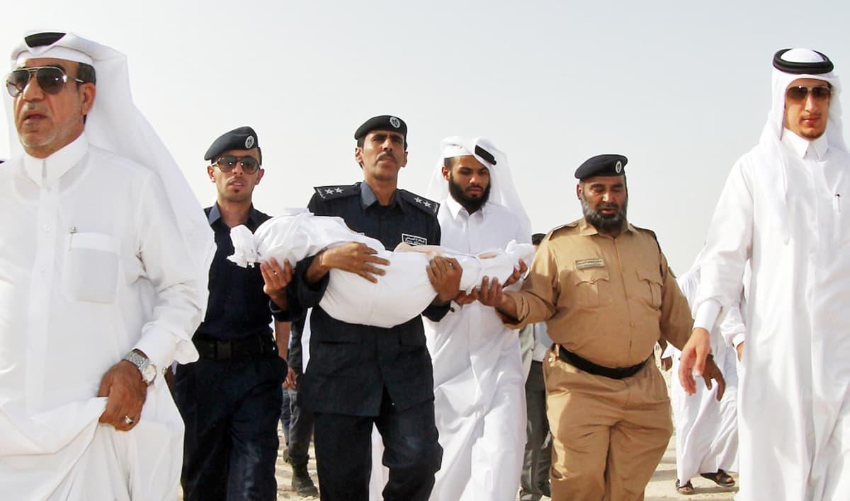 Miehet kantavat ostoskeskuspalon lapsiuhrin ruumista.