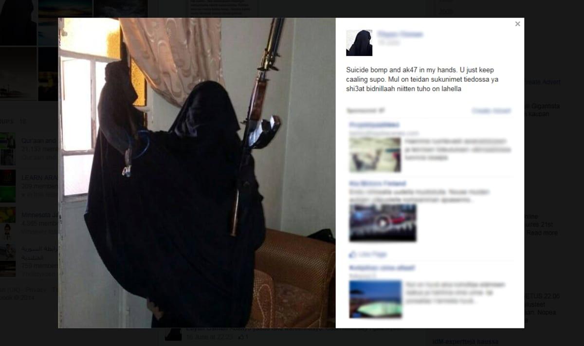 Burkhaan pukeutunut nainen poseeraa aseen kanssa facebook-sivustollaan.