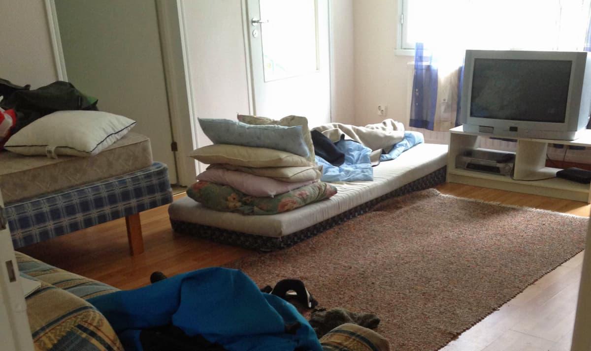 Punkka lattialla, päällä paksu tyynypino.