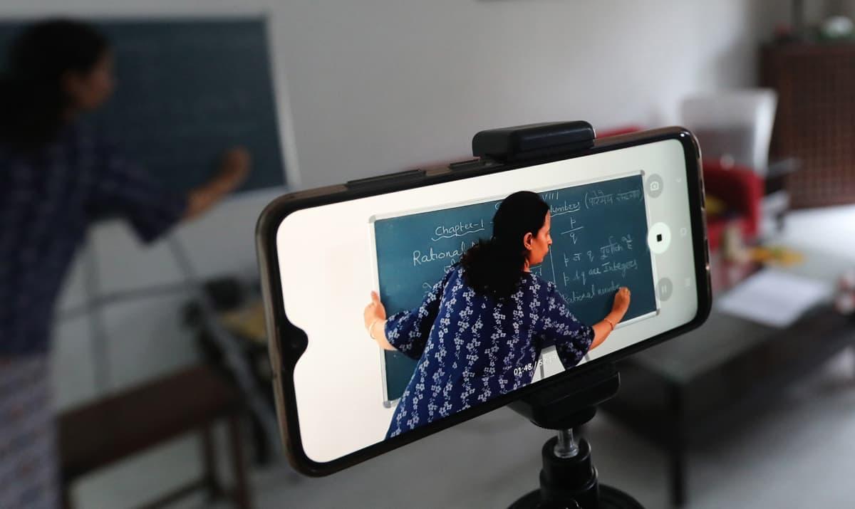 Intialainen opettaja tallentaa matematiikan tuntia puhelimella tyhjässä luokassa oppilaiden käyttöön.