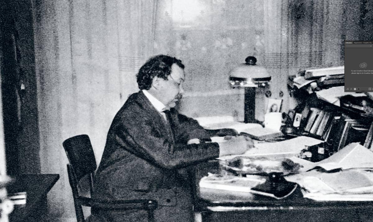 mies kirjoituspöydän ääressä