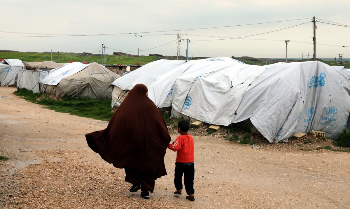 Hunnutettu nainen taluttaa pientä poikaa pakolaisleirin telttojen vieressä.