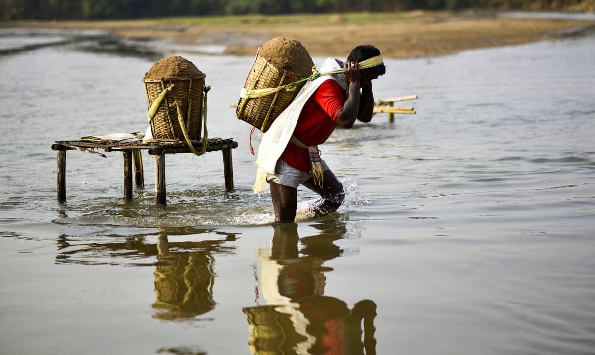 mies kantaa korilla selässään hiekkaa