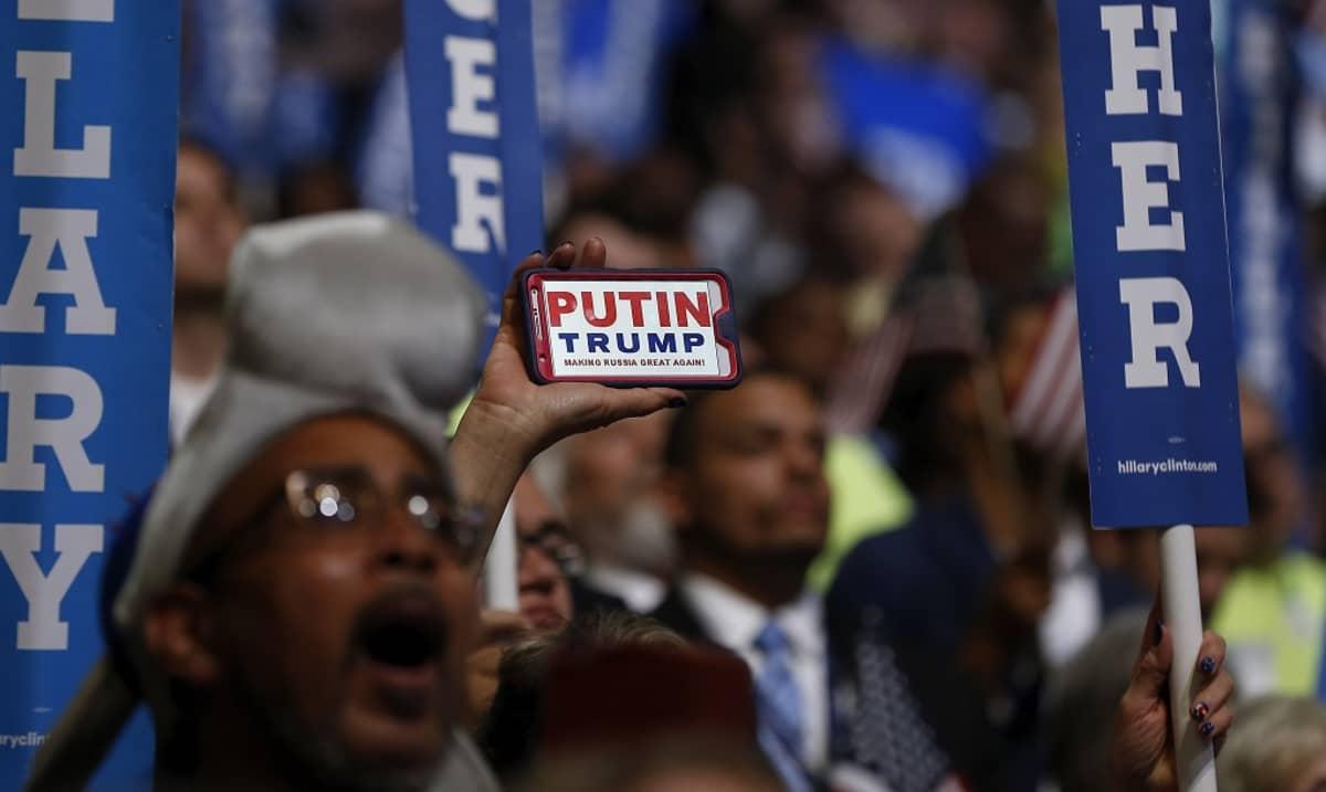 """Kuva ihmismassasta Philadelphian puoluekokouksessa. Väkijoukon keskellä joku pitää esillä kännykkää, jonka näytöllä lukee: """"Putin. Trump. Making Russia Great Again."""""""