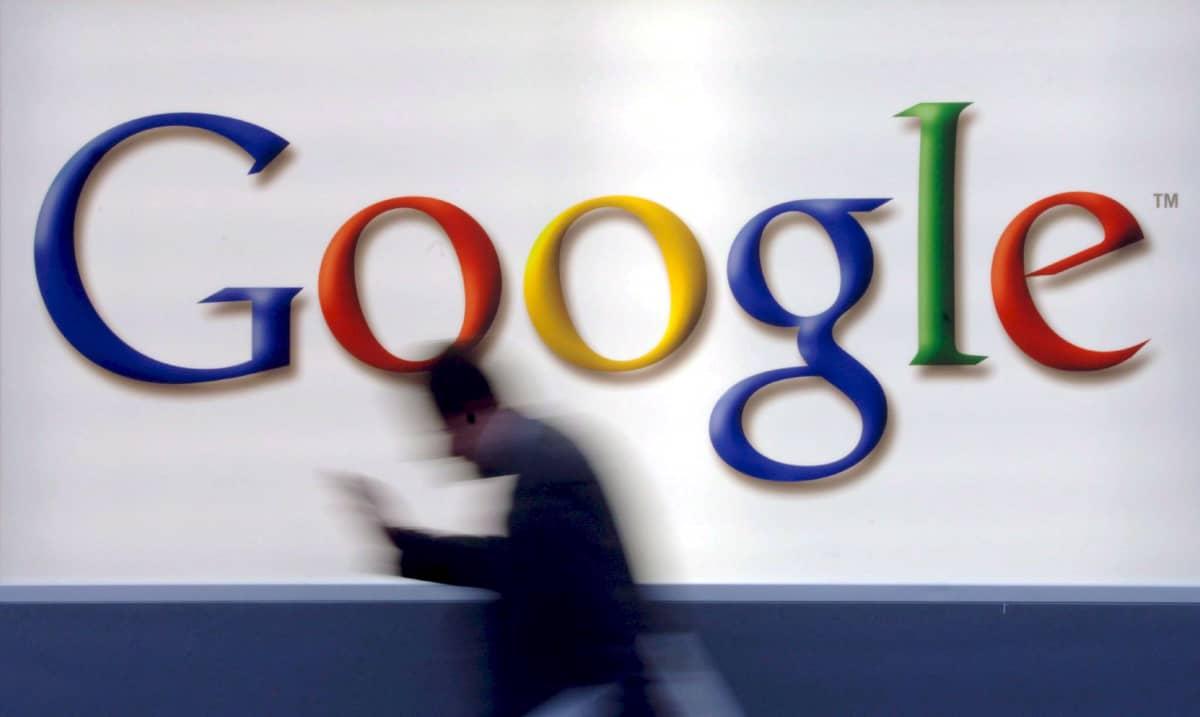 Mies kulkee Googlen logon editse matkapuhelin kädessään.