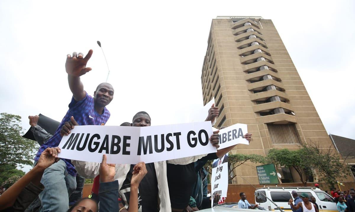"""Mielenosoittajat vaativat presidentti Robert Mugaben eroa Zimbabwen pääkaupungissa Hararessa 18.11.2017. Kuvassa myös juliste, jossa lukee """"Mugaben on mentävä""""."""