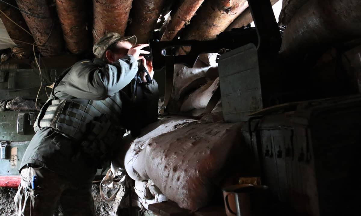 Sotilas tähystää kiikareille ulos poterosta.