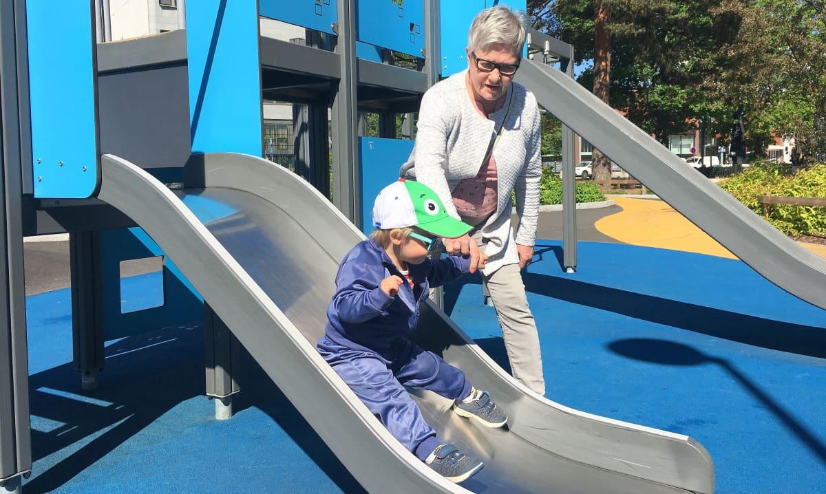 leikkipuisto Hampsta Kouvolan keskustassa, lapsi liukumäessä, mummo auttaa, Eetu ja Hannele Holopainen