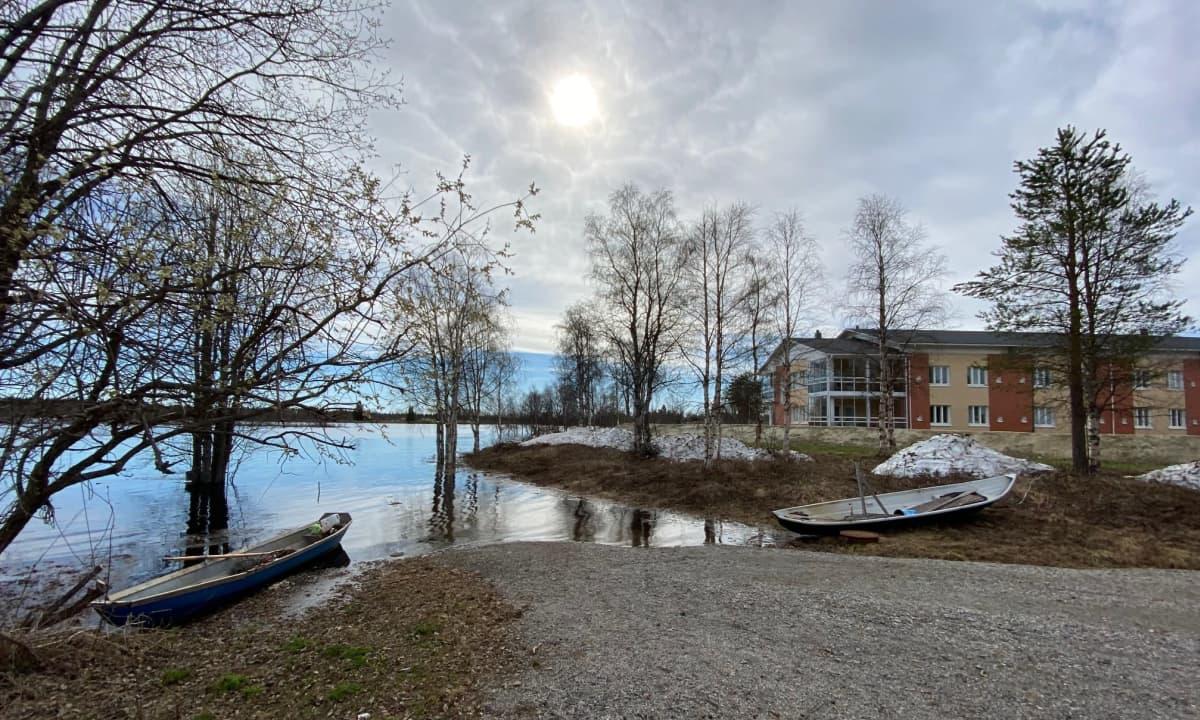 Ounasjoen vesi nousee ja tulvapenger suojaa taustalla olevaa Kittilän terveyskeskusta.