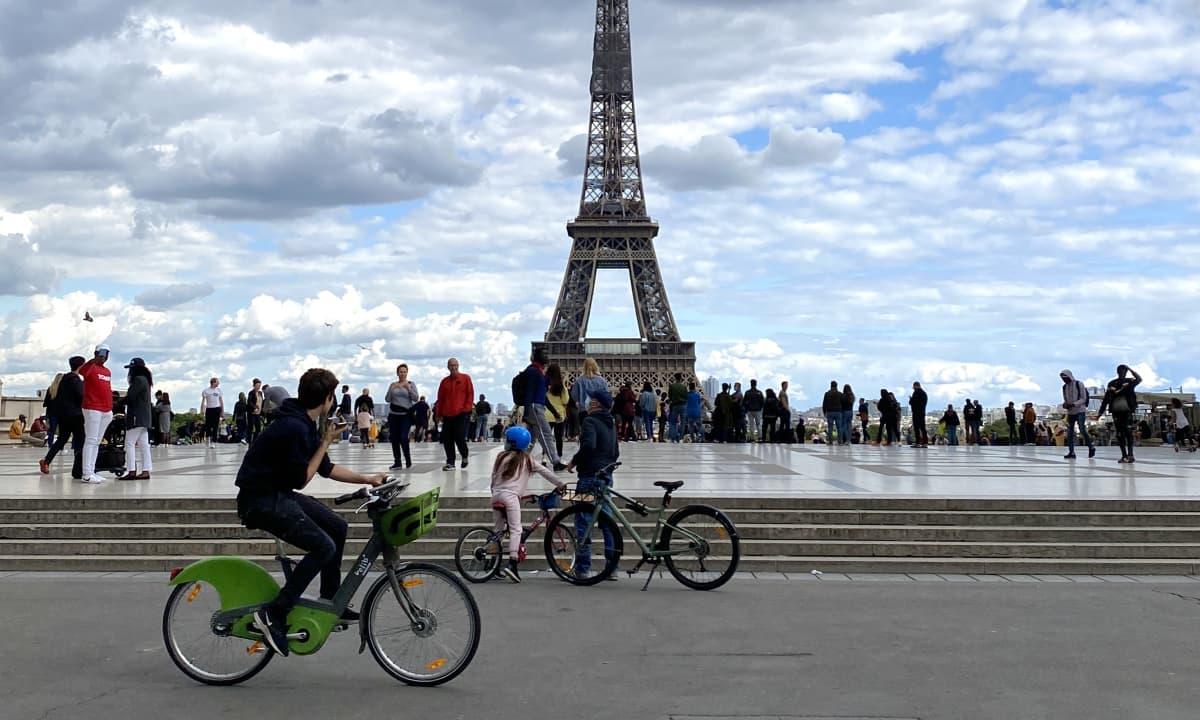 Ihmisiä pyöräilemässä Eiffel-tornin edessä
