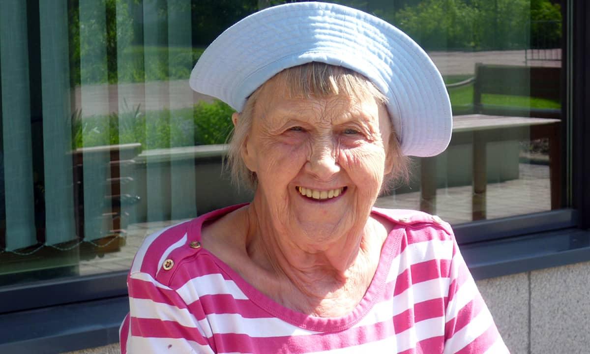 Seniorinainen hymyilee aurinkoisesti auringonpaisteessa.