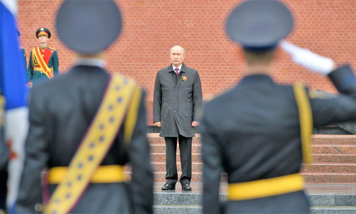 Sotilaat tekevät kunniaa Putinille, joka seisoo harmaassa päällystakissa portailla. Takana näkyy Kremlin punainen muuri.