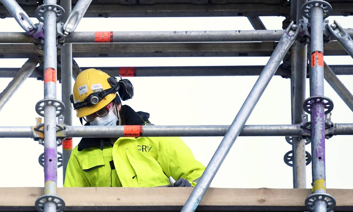 Maskia käyttävä rakennustyömies SRV:n Loisto-tornitalon rakennustyömaalla Helsingin Kalasatamassa 5. maaliskuuta 2021.