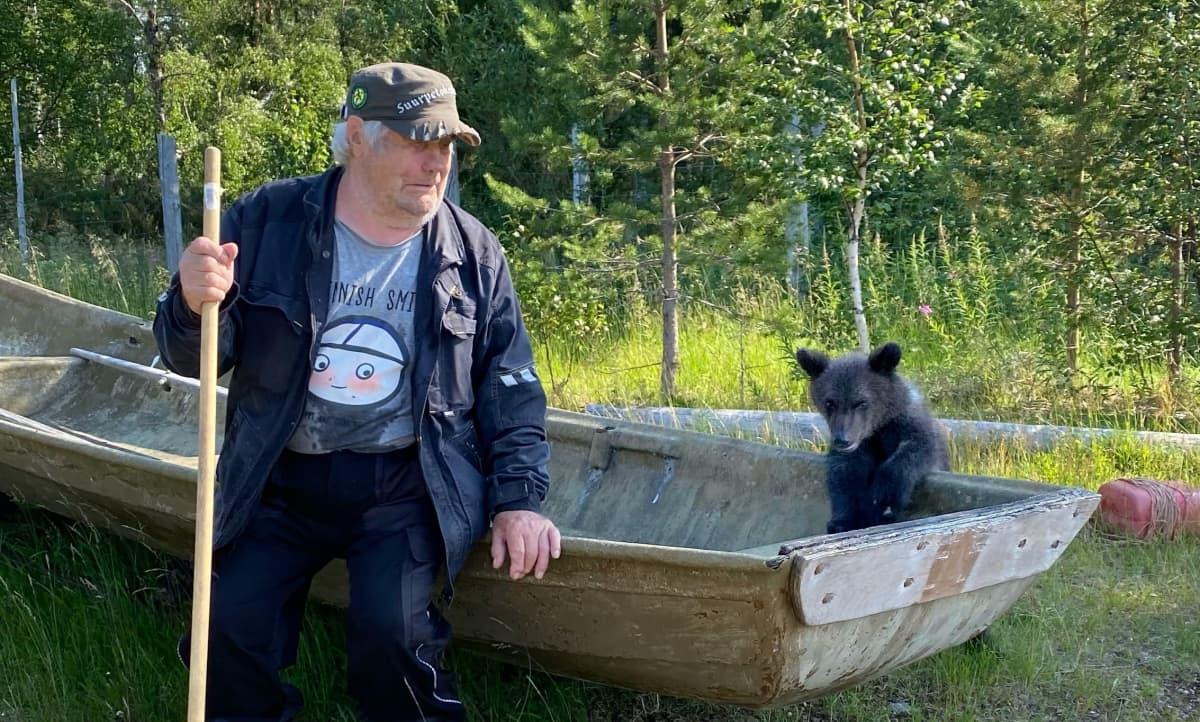 Aina karhunpentu ja Sulo Karjalainen tutustuvat vanhaan veneeseen Kuusamon suurpetokeskuksen rannassa.