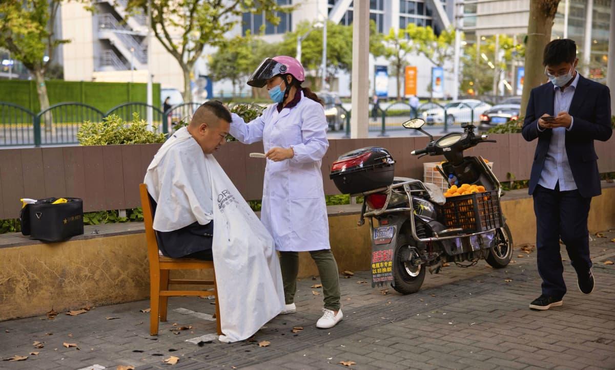 Miehen hiuksia leikataan kadulla Shanghain pörssin edessä