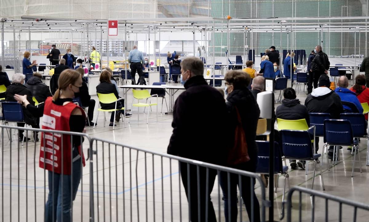 Ihmisiä ja työntekijöitä Ouluhallin koronarokotuksissa.