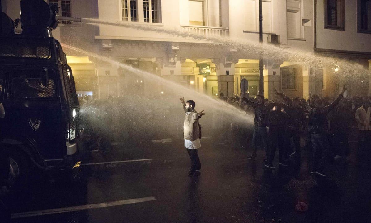 Poliisit, vesitykki ja mielenosoittajat.