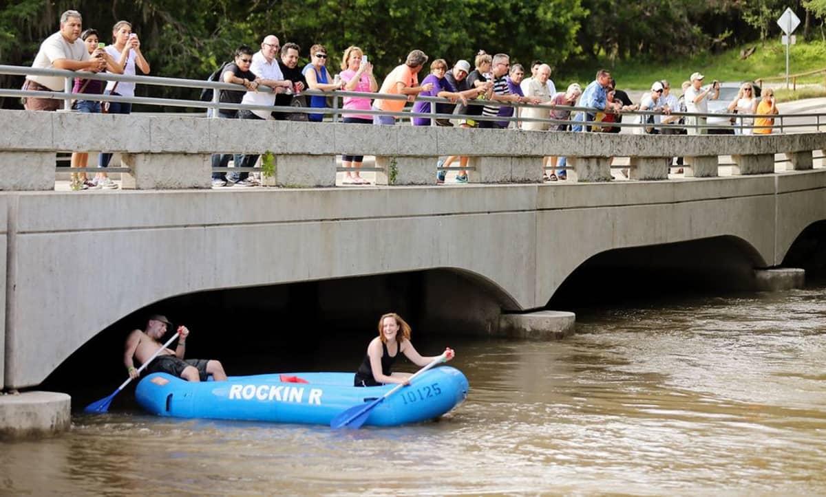 Ihmisiä tulvivan joen Guadalupe-joen äärellä Gruenessa Texasissa 23. toukokuuta.
