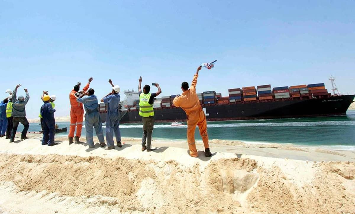Egyptiläiset työntekijät vilkuttivat konttialukselle, joka kulki uudella Suezin kanavalla Ismailian kaupungissa Egyptissä 25. heinäkuuta.