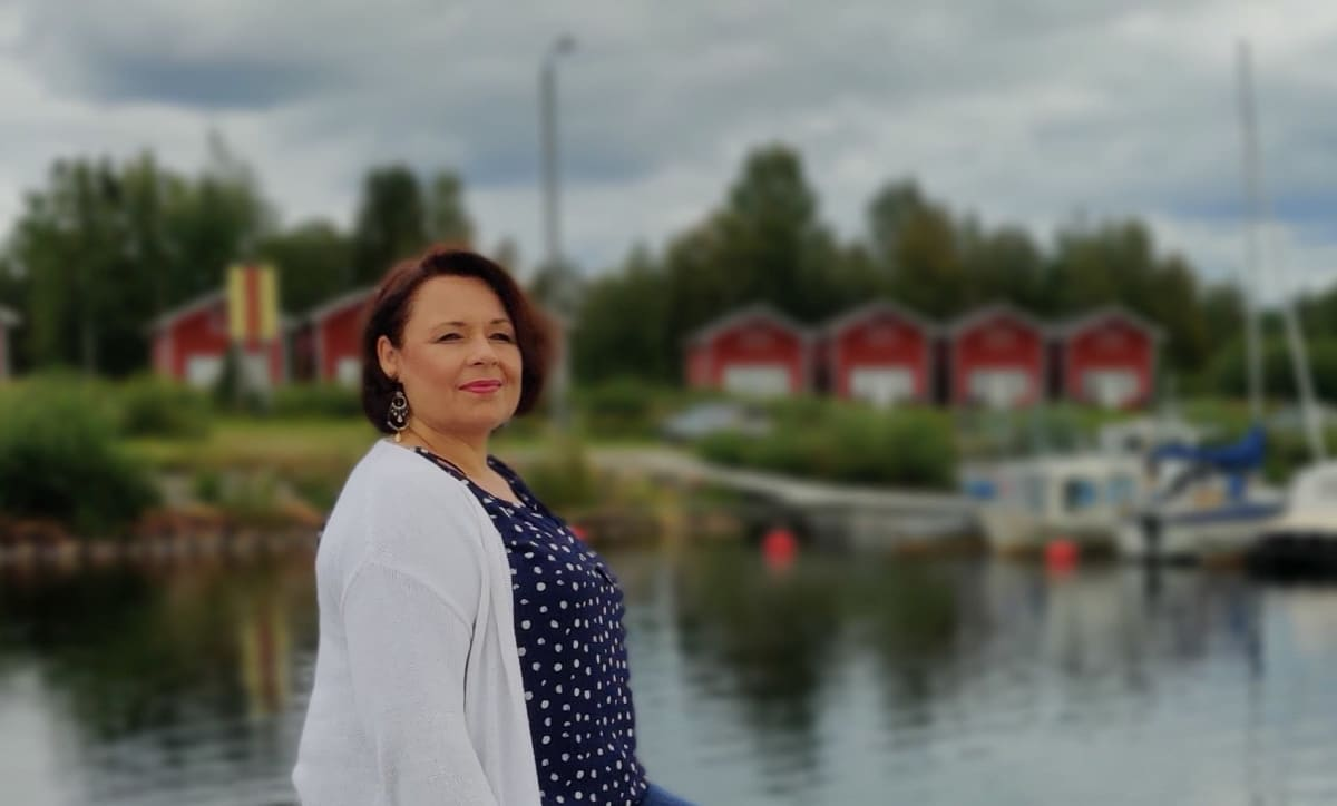 Oopperalaulaja Tuija Knihtilä Simon venesatamassa, taustalla aittarakennuksia.